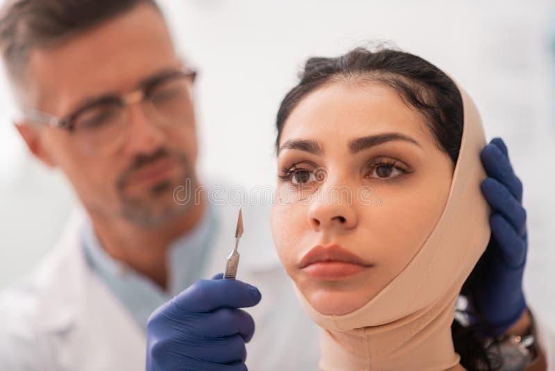 Fasciatura d'uso della donna di affari sul fronte prima di chirurgia plastica immagine stock
