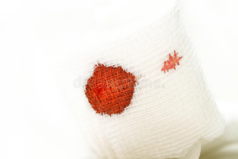 Fasciatura della garza con sangue su bianco fotografie stock