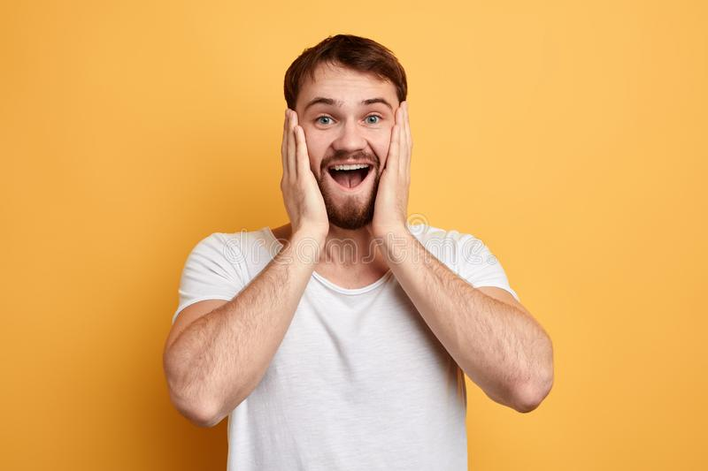 Fascinated excited cheerful man with palms on his cheek expresses happiness royalty free stock photos
