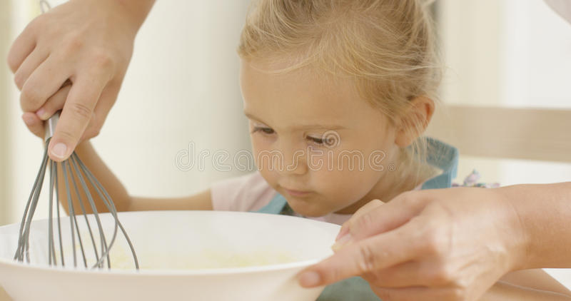 Fascinated little girl learning to bake stock images