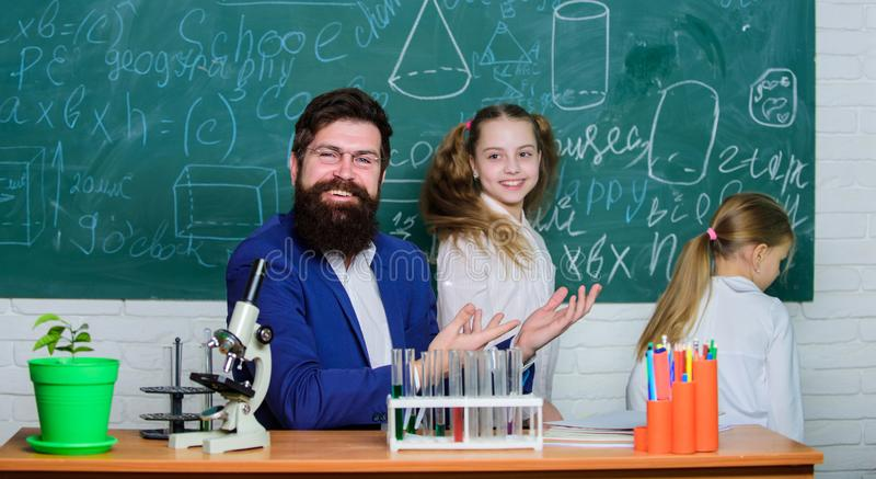 Fascinating biology lesson. School teacher of biology. Man bearded teacher work with microscope and test tubes in. Biology classroom. How to interest children royalty free stock image