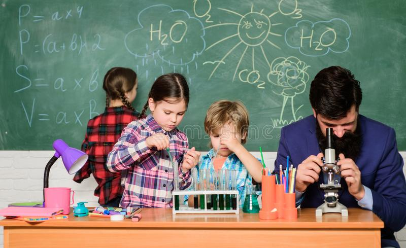 Fascinating chemistry lesson. Man bearded teacher and pupils with test tubes in classroom. Observe reaction. Science is. Always the solution. School chemistry stock photos
