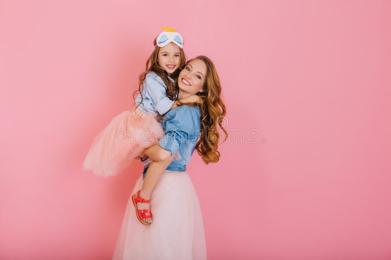 Fascinating curly mother and beautiful trendy daughter in the same outfit posing together after birthday party. Portrait stock images