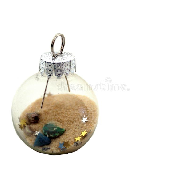 Nautical Glass Ball Ornament with Sand, Shells and Glitter. A fascinating glass ball ornament with sand, shells and glitter. Used to hang on a Christmas tree or royalty free stock photo