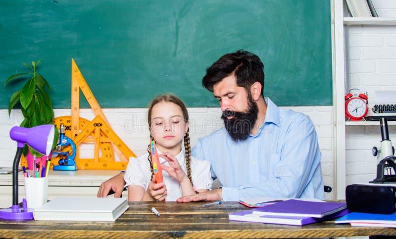 Fascinating lesson. Explaining science to child. School teacher and schoolgirl. Man bearded teacher excellent pedagogue. Pedagogue skills. Talented pedagogue stock image