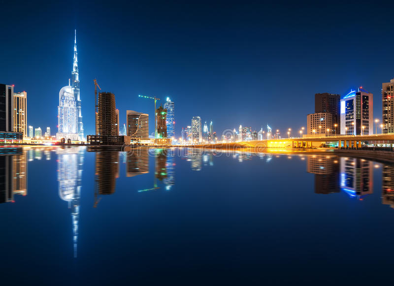 Fascinating reflection of tallest skyscrapers in Business Bay district during calm night. Dubai, United Arab Emirates. stock image