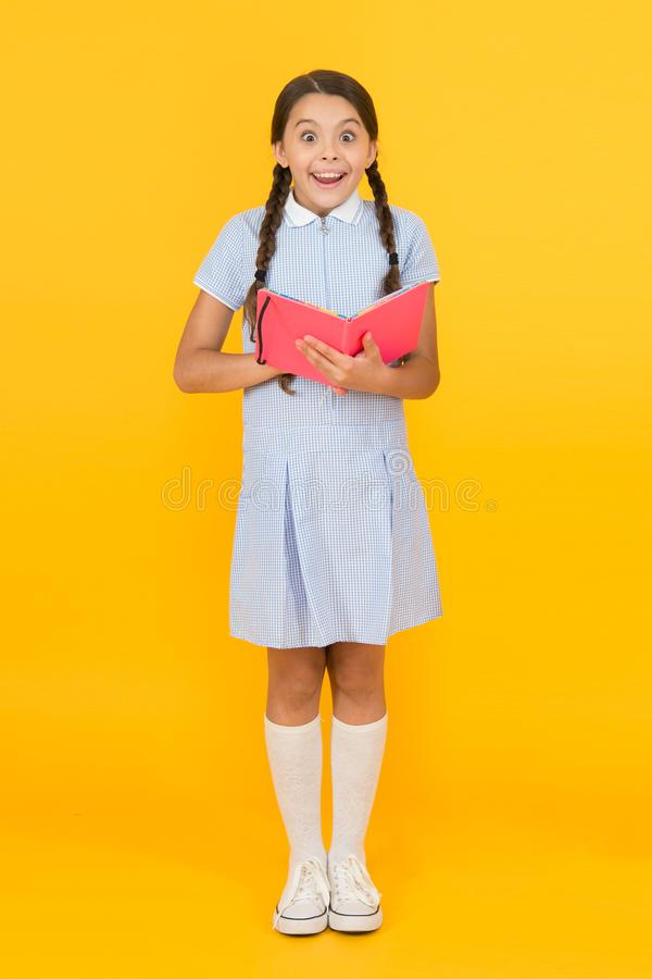 Fascinating story. small girl love literature. old school. happy little girl in retro uniform. vintage kid fashion. back. To school. small girl hold workbook or stock images