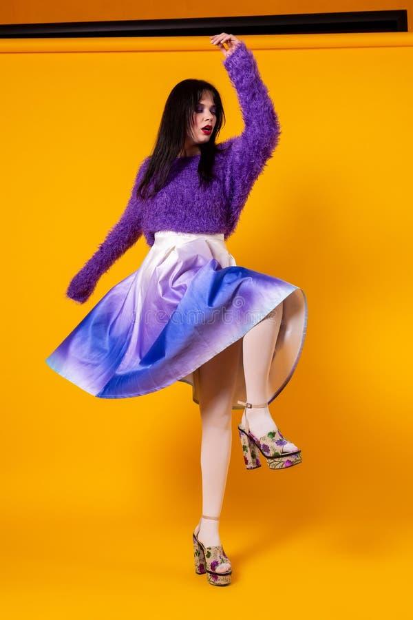 Fascinera hipsterflickan i purpurfärgad dräkt som spenderar tid i studio med den gula väggen royaltyfri foto