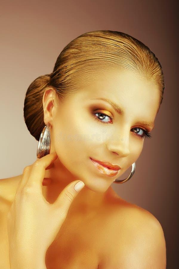Fascinerande dam med silverörhängen och silkeslen guld- hud fotografering för bildbyråer