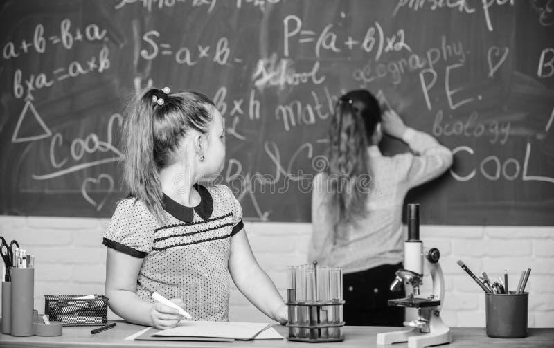 Fascinerende wetenschap Onderwijsexperiment De meisjesklasgenoten bestuderen chemie De chemische reacties van microscoopreageerbu stock fotografie