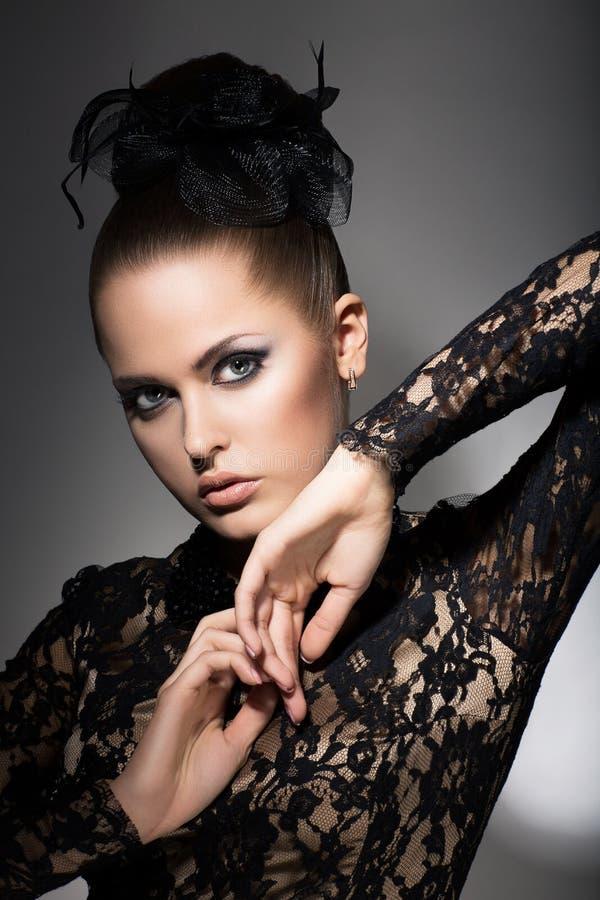 Fascino. Donna lussuosa in vestito e nell'arco neri. Sofisticazione immagini stock