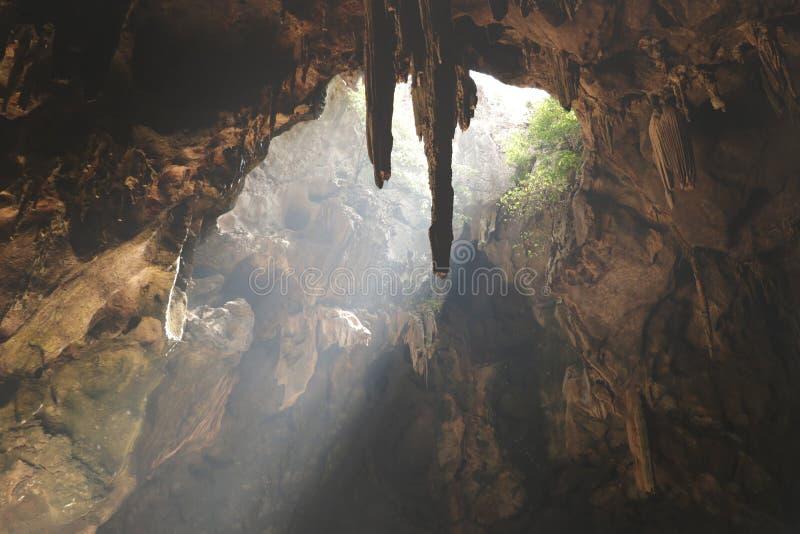 Fascio luminoso naturale attraverso un foro in una caverna fotografia stock