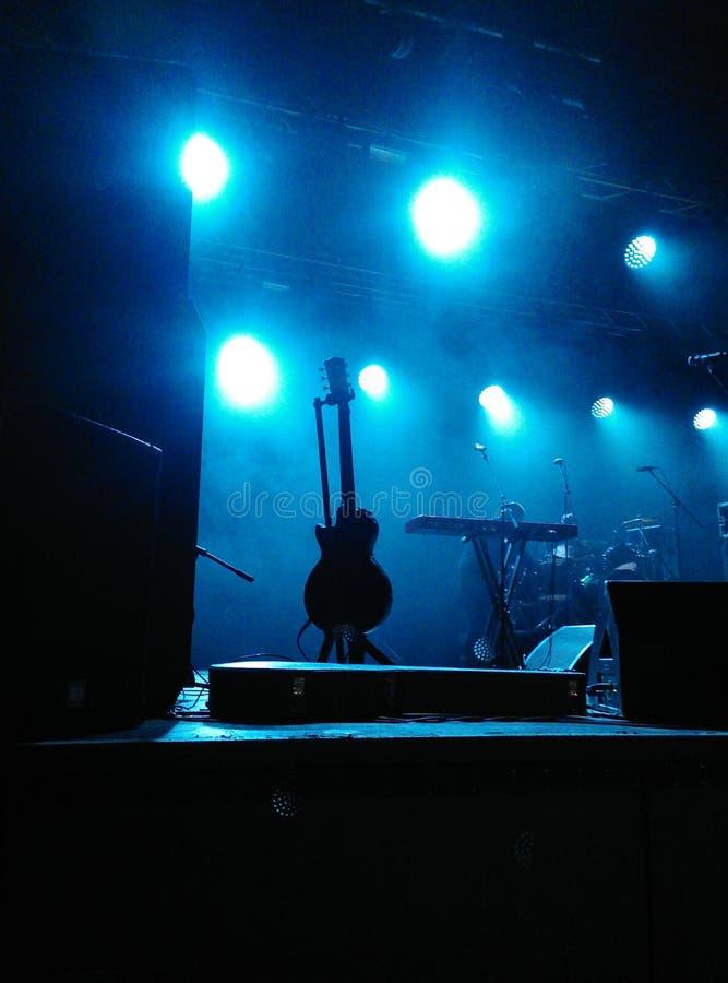 Fase com o silouette preto da guitarra estando com microfones e outros instrumentos musicais sob os projetores azuis penugem imagens de stock royalty free