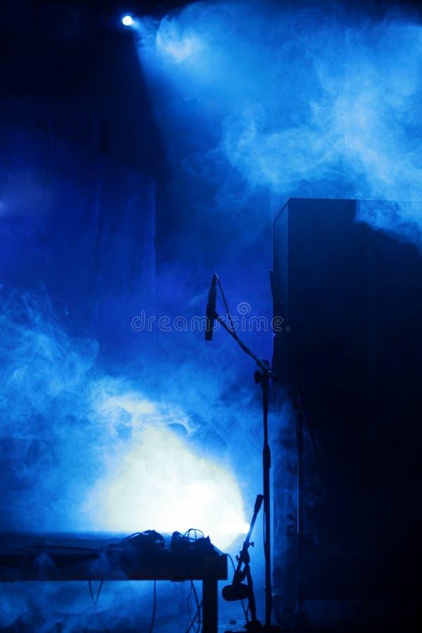 Fase con il microfono e l'indicatore luminoso blu immagini stock