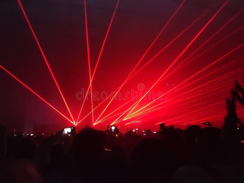 Fase do clube da vida noturno da mostra do laser com a multidão dos povos do partido entretenimento com as silhuetas da audiência foto de stock