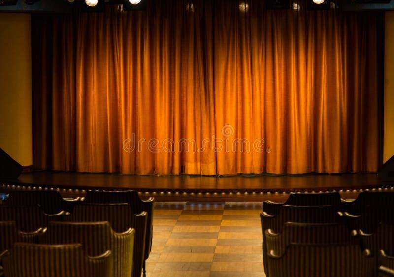 Fase pequena com as cortinas alaranjadas no cinema privado cameral fotografia de stock