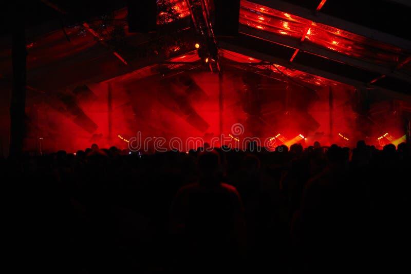 Fase temperamental escura, fãs enormes como suportes da fase, luzes vermelhas, multidão irreconhecível fotografia de stock royalty free