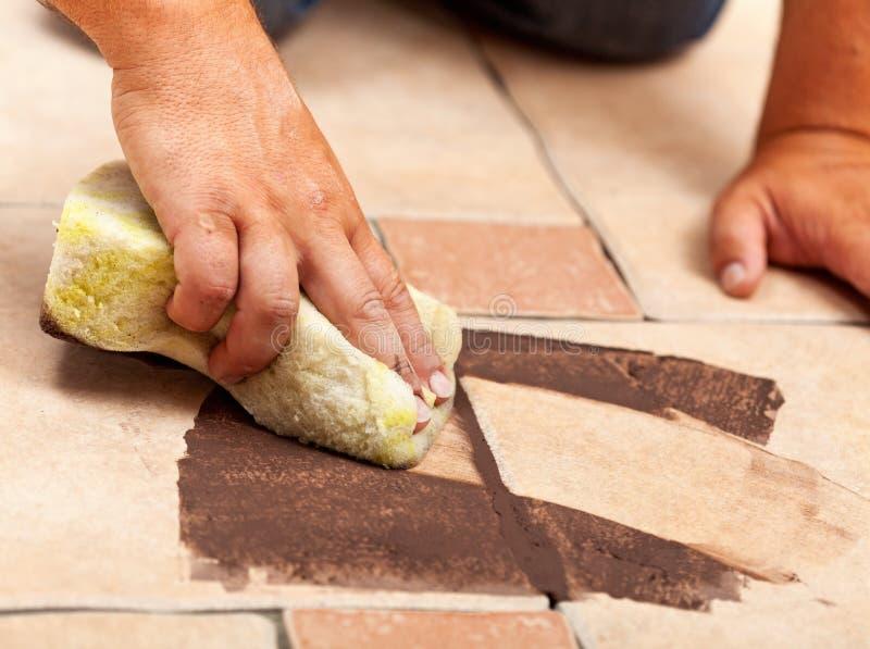 Faser av installation av det keramiska golvet som belägger med tegel - det gemensamma materialet royaltyfri bild
