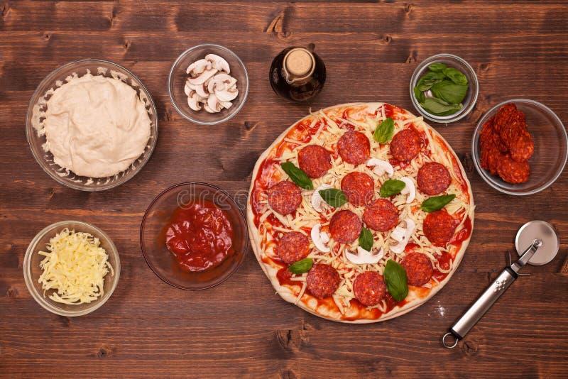 Fases de hacer una pizza - la pizza lista para cocer, visión superior fotografía de archivo libre de regalías