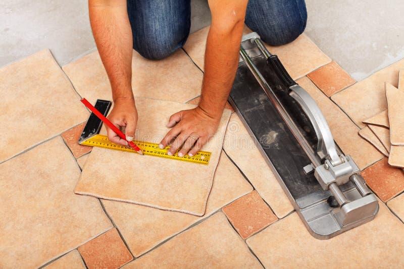 Fases de instalar telhas de assoalho cerâmicas - cortando as partes fotografia de stock