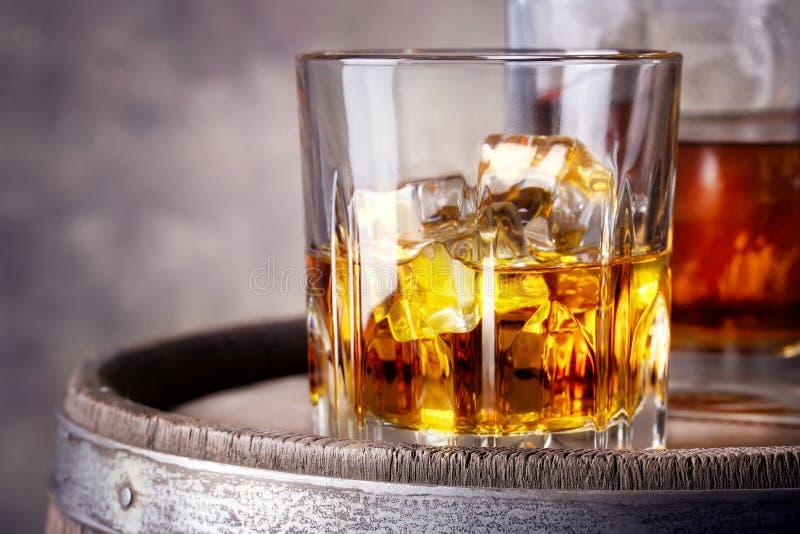 Fasetterat exponeringsglas av whisky med is royaltyfri fotografi