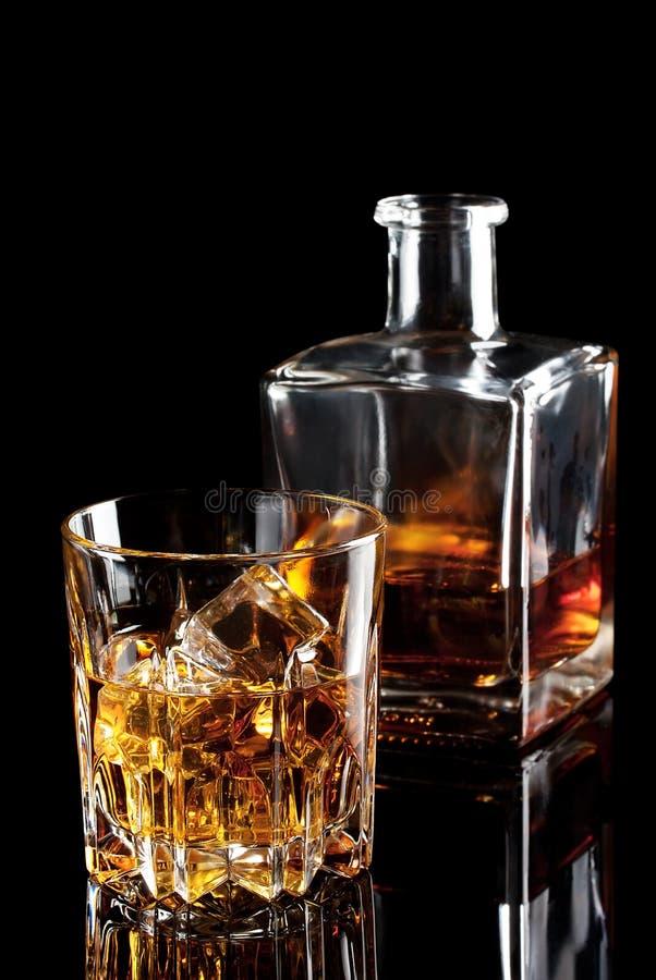 Fasetterat exponeringsglas av whisky med is och en flaska royaltyfri bild