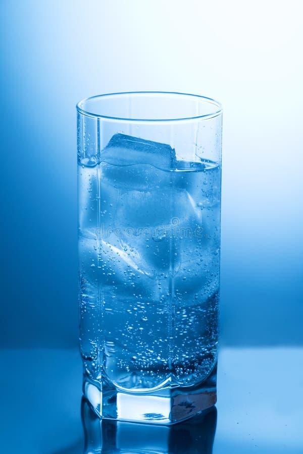 Fasetterat exponeringsglas med rent vatten och is på den blåa bakgrunden arkivfoton