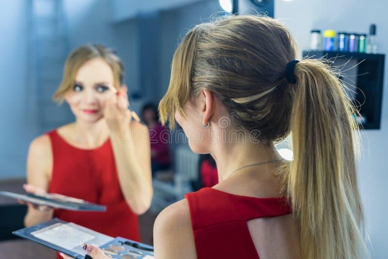 Fashio-Porträt des schönen jungen Mädchens, das Make-up nahe Spiegel macht lizenzfreies stockfoto
