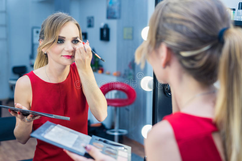 Fashio Portrait of beautiful young girl making make-up near mirror stock images