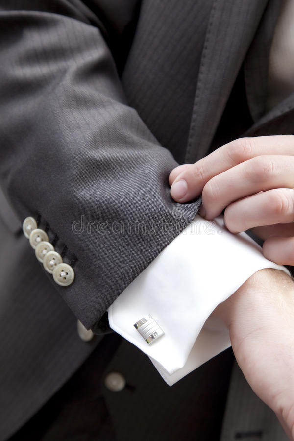 Fashion. Men's fashion. Dark grey suit, white shirt with silver cuff-links stock image