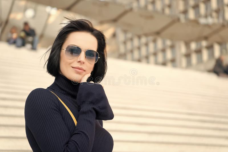 Fashion and accessory. Woman in sunglasses on stairs. Ambition, challenge, success concept. Girl with brunette hair in black clothes. Look, beauty, style stock photo