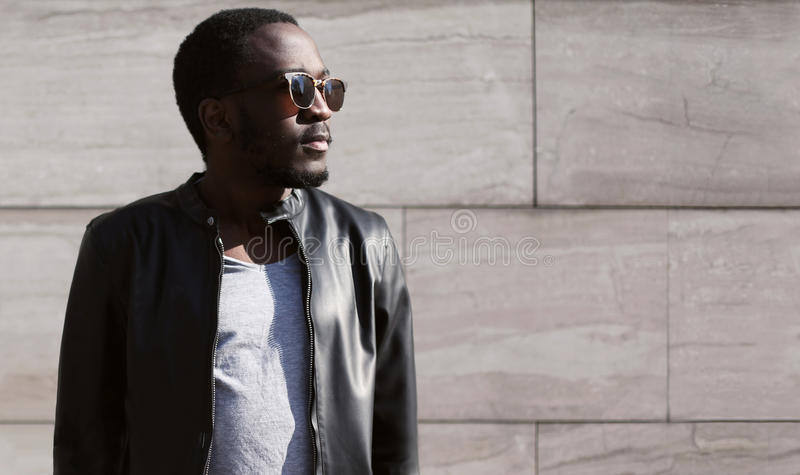 Fashion african man wearing a sunglasses and black rock leather jacket over textured background evening in city. Fashion young african man wearing a sunglasses stock photography