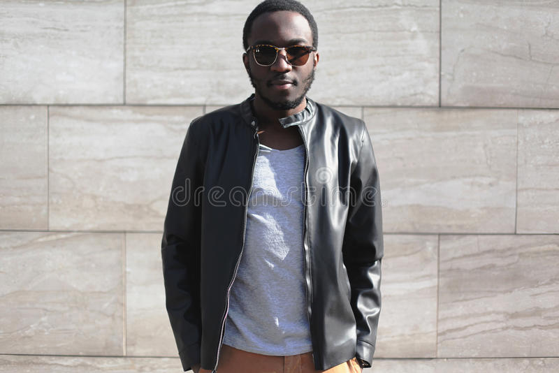 Fashion african man wearing a sunglasses and black rock leather jacket over textured gray background in city stock photography