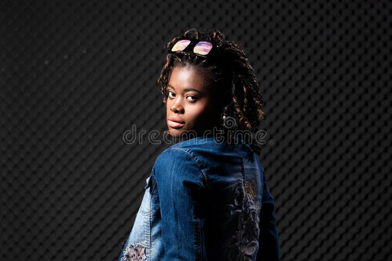 African Teenager Woman Tan skin black Afro hair. Fashion African Teenager Woman Tan skin black Afro hair beautiful high fashion make up sunglasses pink vast Jean royalty free stock images