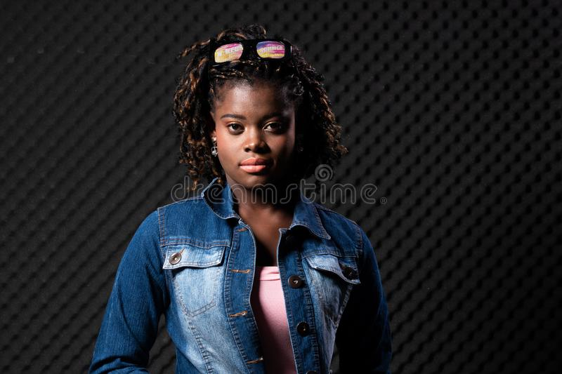 African Teenager Woman Tan skin black Afro hair. Fashion African Teenager Woman Tan skin black Afro hair beautiful high fashion make up sunglasses pink vast Jean stock image