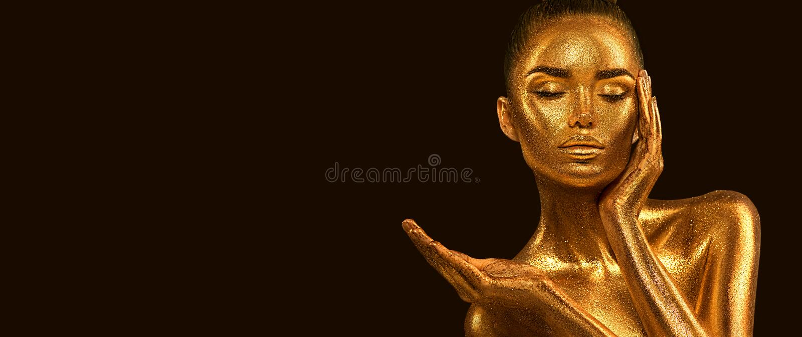 Fashion art Golden skin Woman face portrait closeup. Model girl with holiday golden Glamour shiny makeup. Sequins. Gold jewellery stock photos