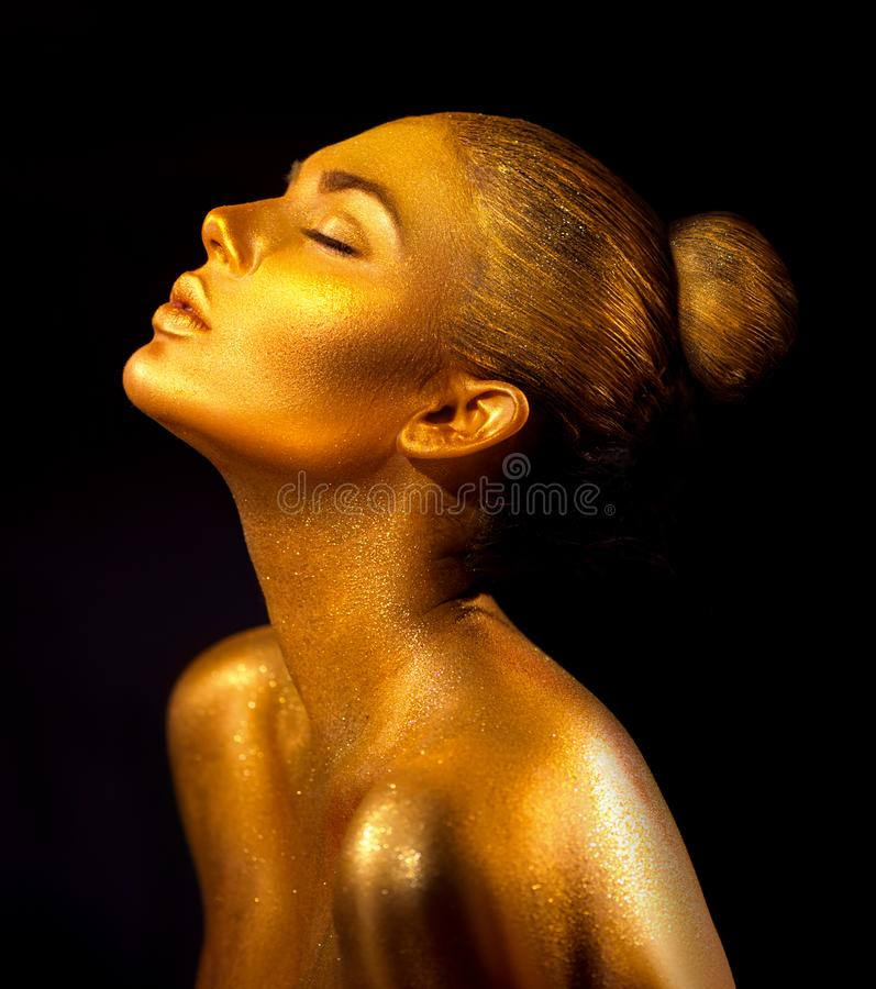 Fashion art golden skin woman portrait closeup. Gold, jewelry, accessories. Model girl with golden shiny makeup stock images