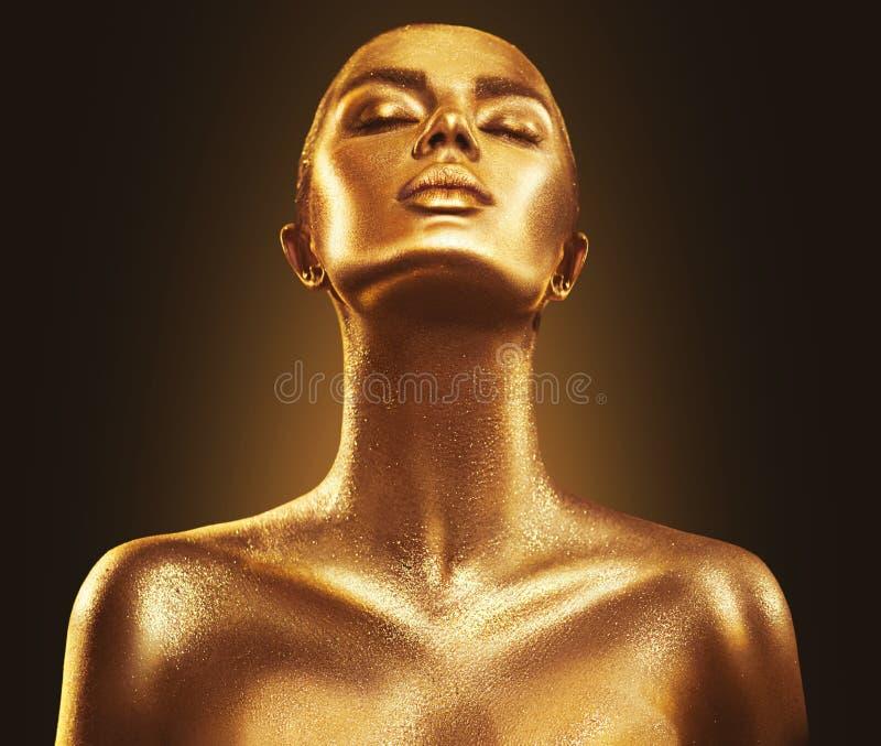 Fashion art golden skin woman portrait closeup. Gold, jewelry, accessories. Model girl with golden shiny makeup. Fashion art golden skin woman portrait closeup
