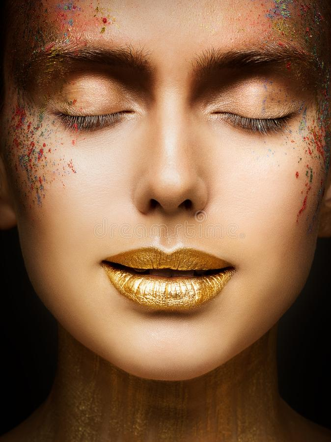 Fashion Art Makeup, Creative Beauty Face Lips Make Up, Gold Lipstick Closed Eyes in Color Dust Paint royalty free stock photography