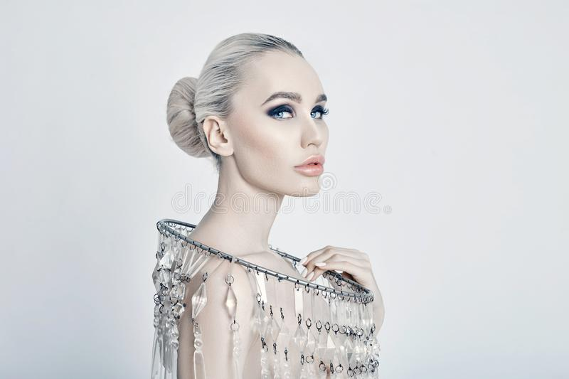 Fashion art portrait of a blonde with a big shiny necklace, Nude woman, skin care, face and body. Creative portrait. stock image