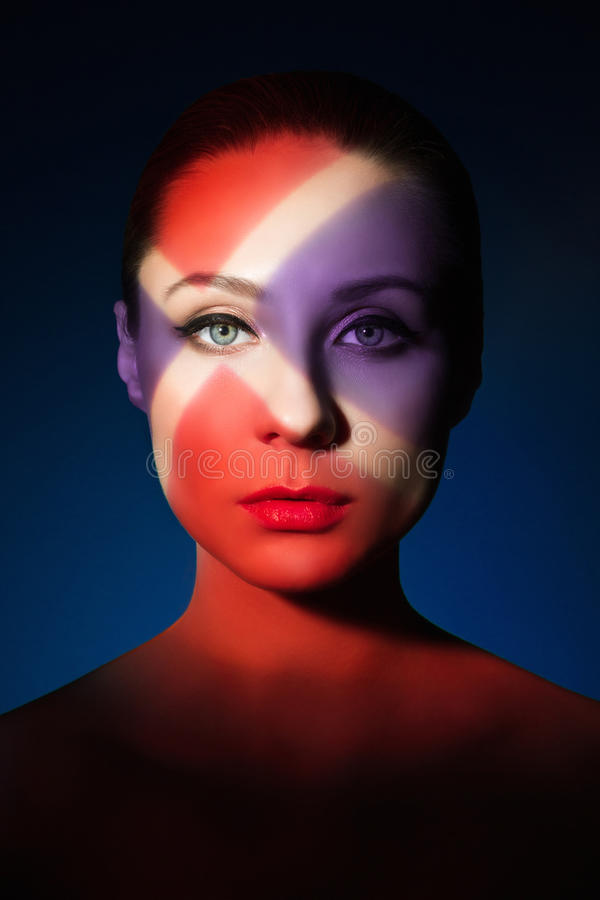 Fashion art portrait of elegant naked young woman. With color light on her face royalty free stock images