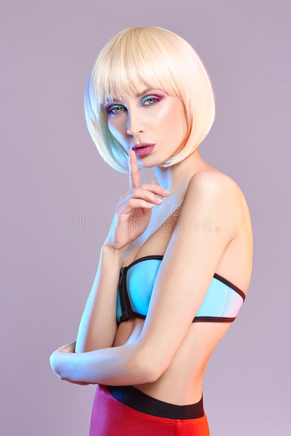 Fashion art portrait of a woman in a swimsuit with bright contrasting makeup. Creative beauty photo of a girl on a contrasting. Background with colored shadows stock image