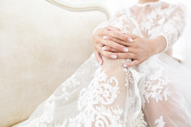 Fashion art portrait woman in transparent white negligee dress. Girl sitting on sofa in peignoir and waits for groom. Bride`s royalty free stock photos