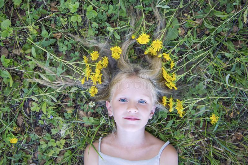 Fashion art portrait young little blonde girl, hair waves lie on the green grass with yellow flowers. Top view, outdoors royalty free stock image