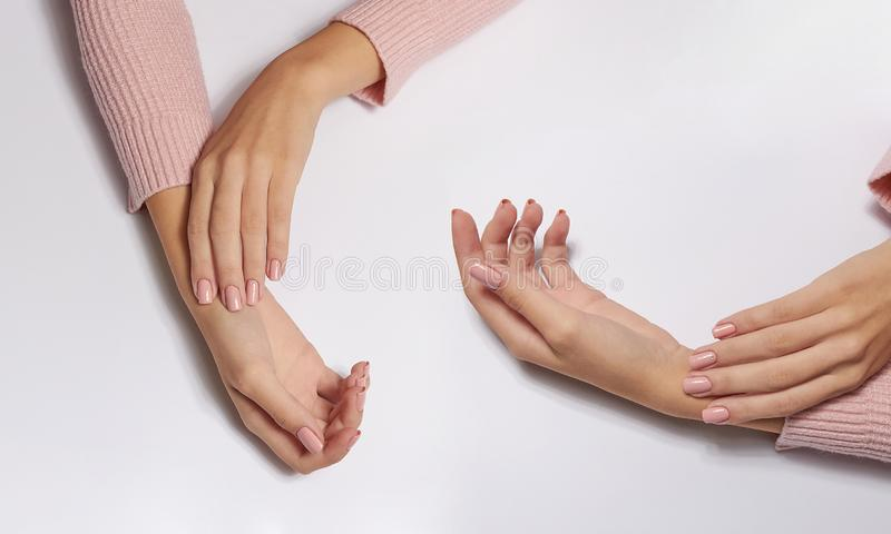 Fashion art skin care of hands and pink flowers in hands of women.  stock image