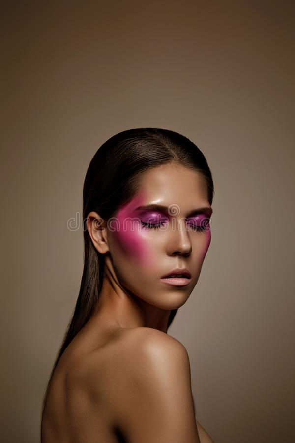 Fashion art skin woman face portrait closeup. Glamour shiny professional makeup girl with trendy pink make-up stock photography