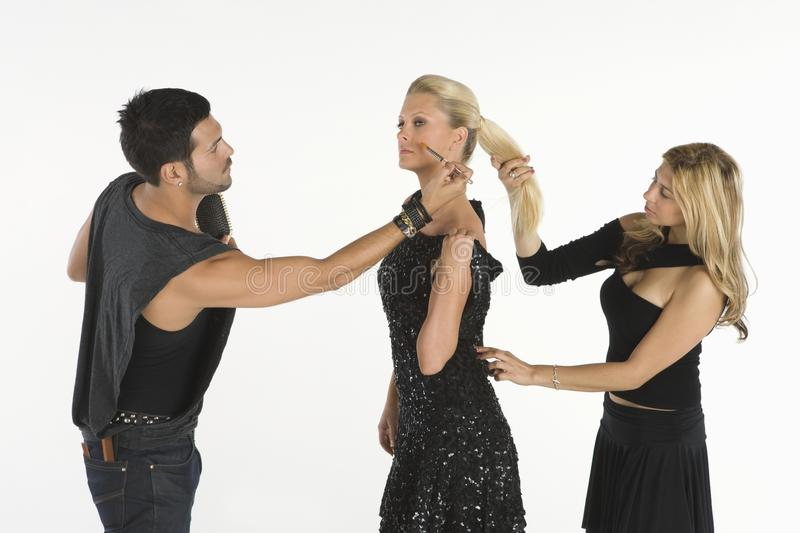 Fashion Artists Assisting Young Female Model. Two fashion artists assisting young female model isolated over white background stock photos
