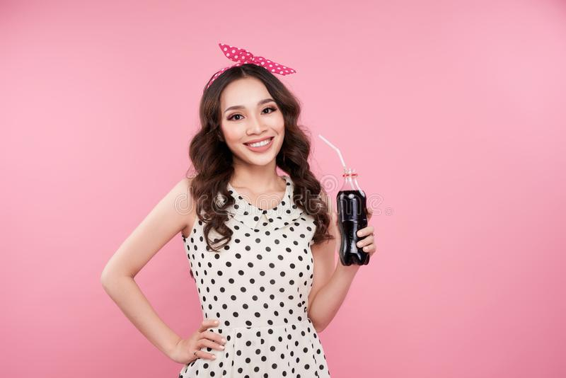 Fashion asian woman holding coke bottle, posing against pink background stock images