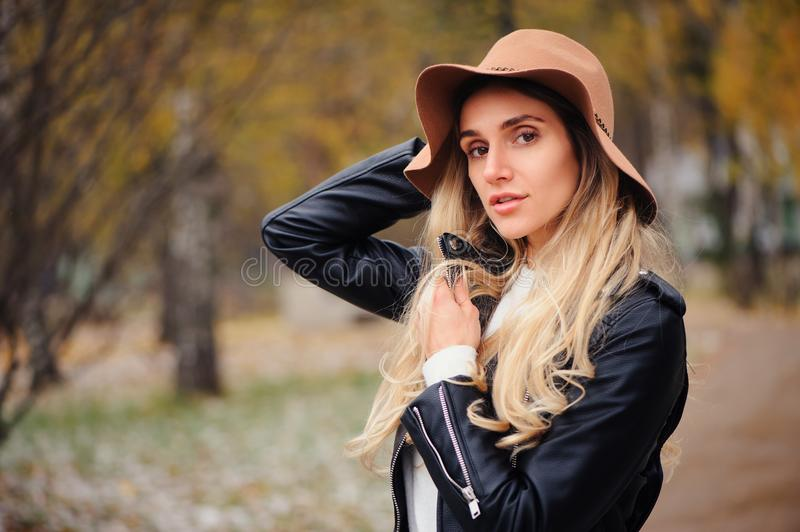 Fashion autumn portrait of young happy woman walking outdoor in fall park stock image