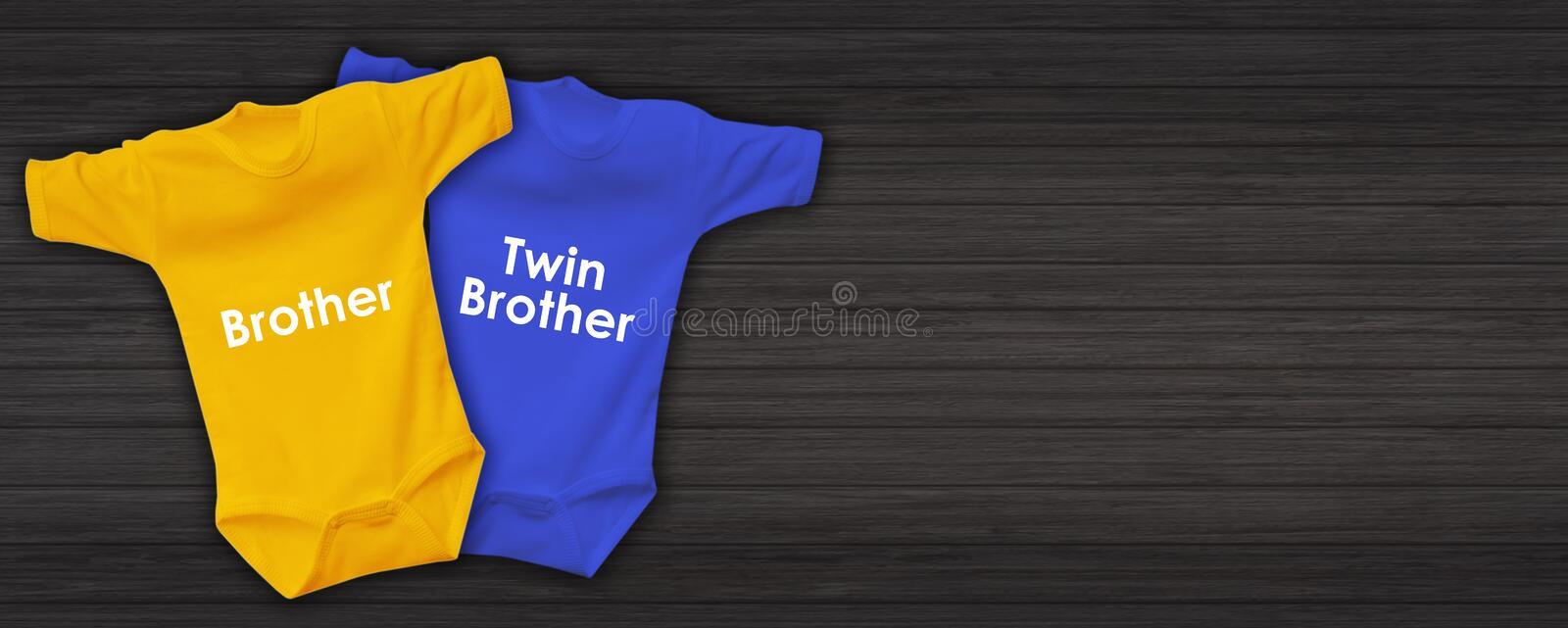 Fashion baby clothing for twin babies with cute trendy newborn bodysuits onesie isolated on dark woden background stock photo
